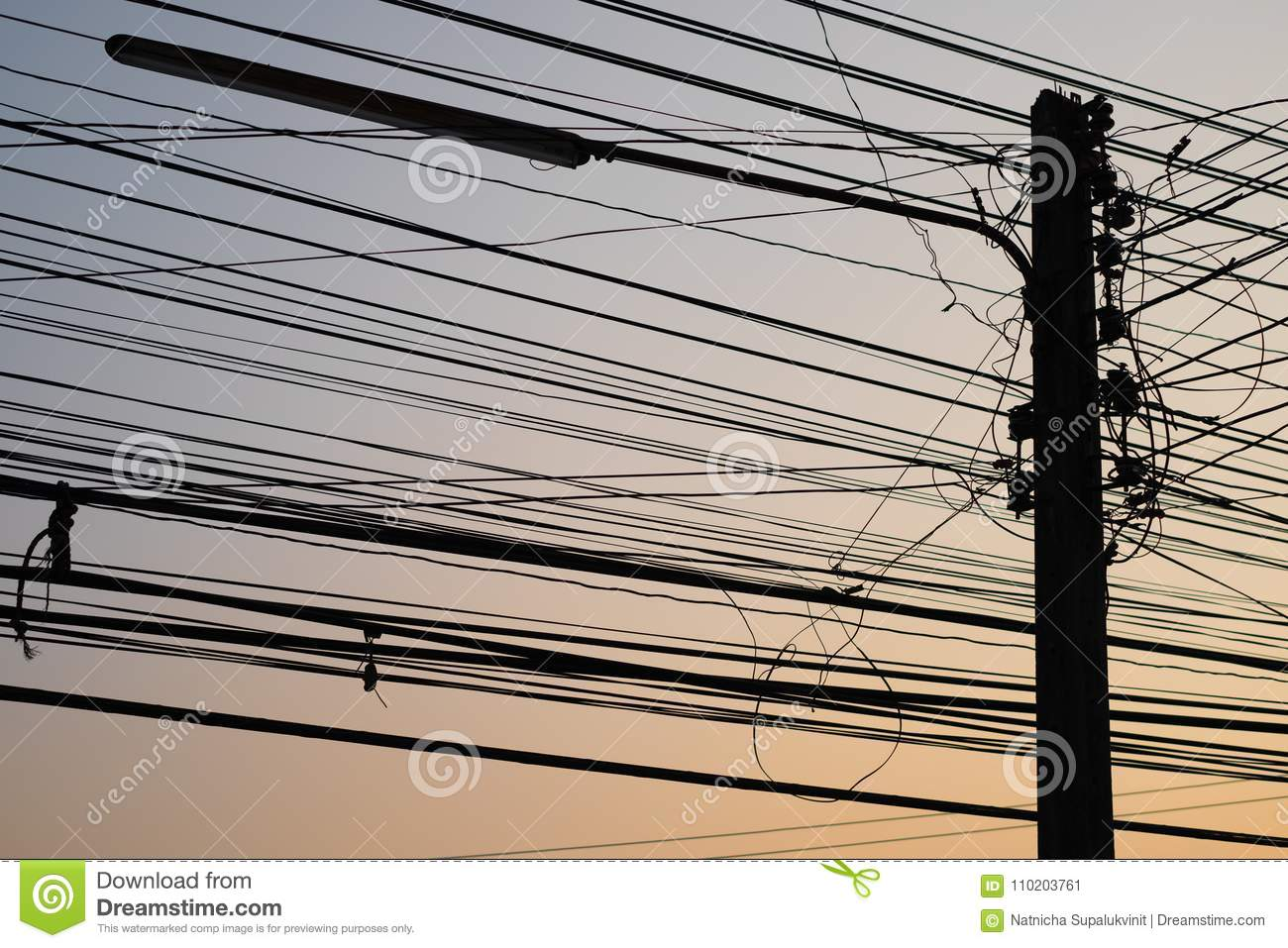 silhouette electric pole with wire and lamp on orange sky in the evening