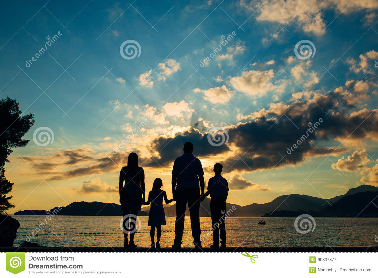 Silhouette of a family with children against the backdrop of the setting sun and sea