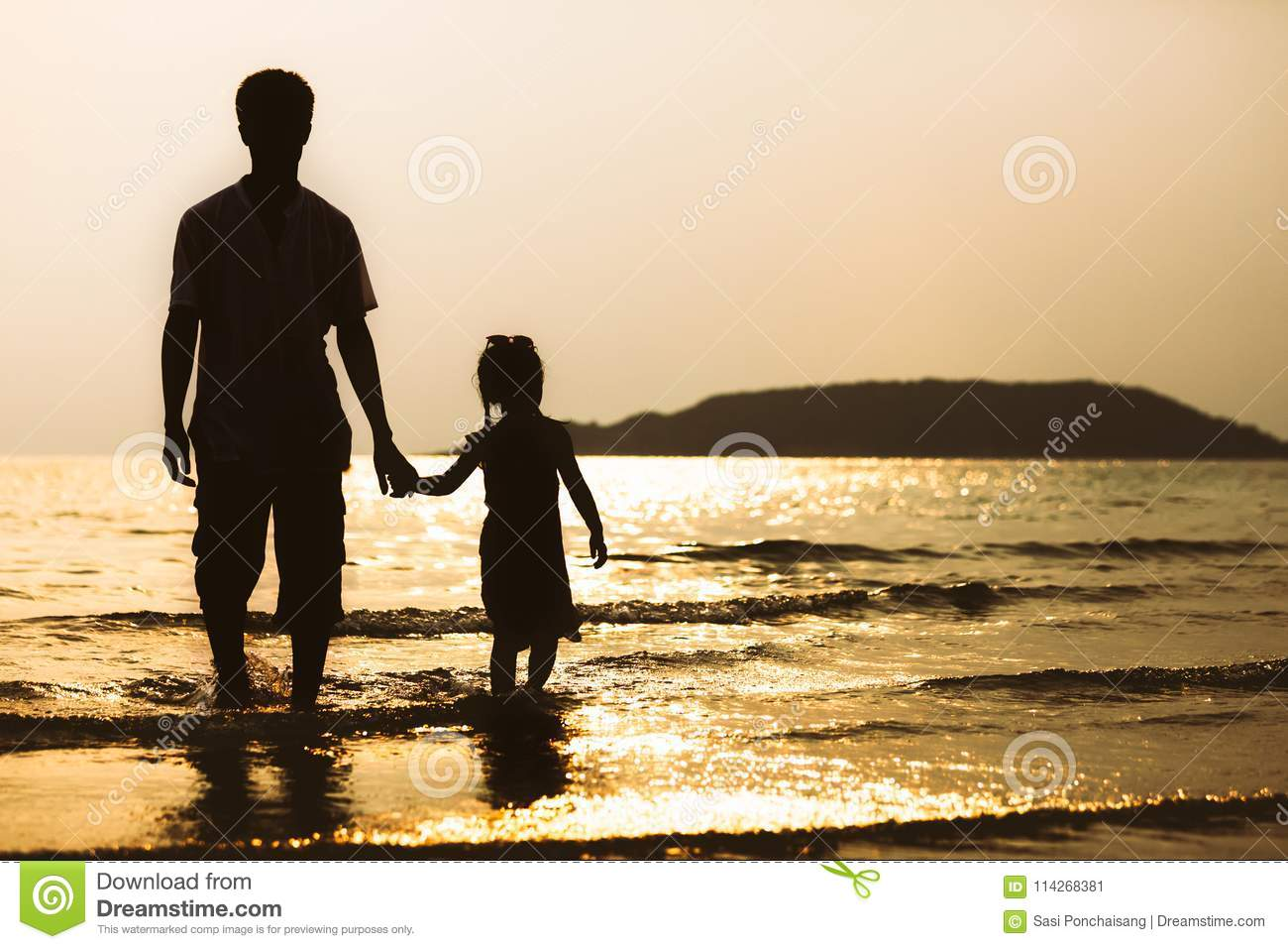 Silhouette Of Father And Daughter Holding Hand And Walking On Beach