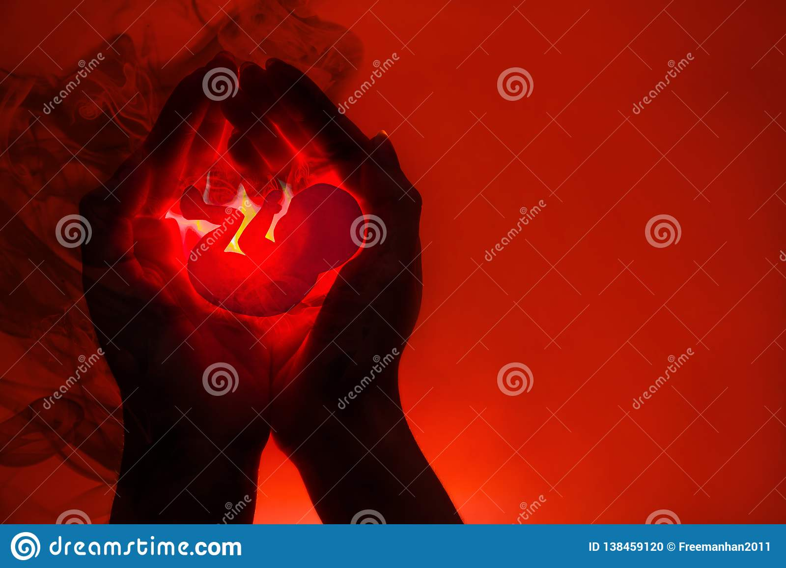 Silhouette of female hands and application in the form of an embryo.The concept of abortion . Hands dissolve in the black smoke