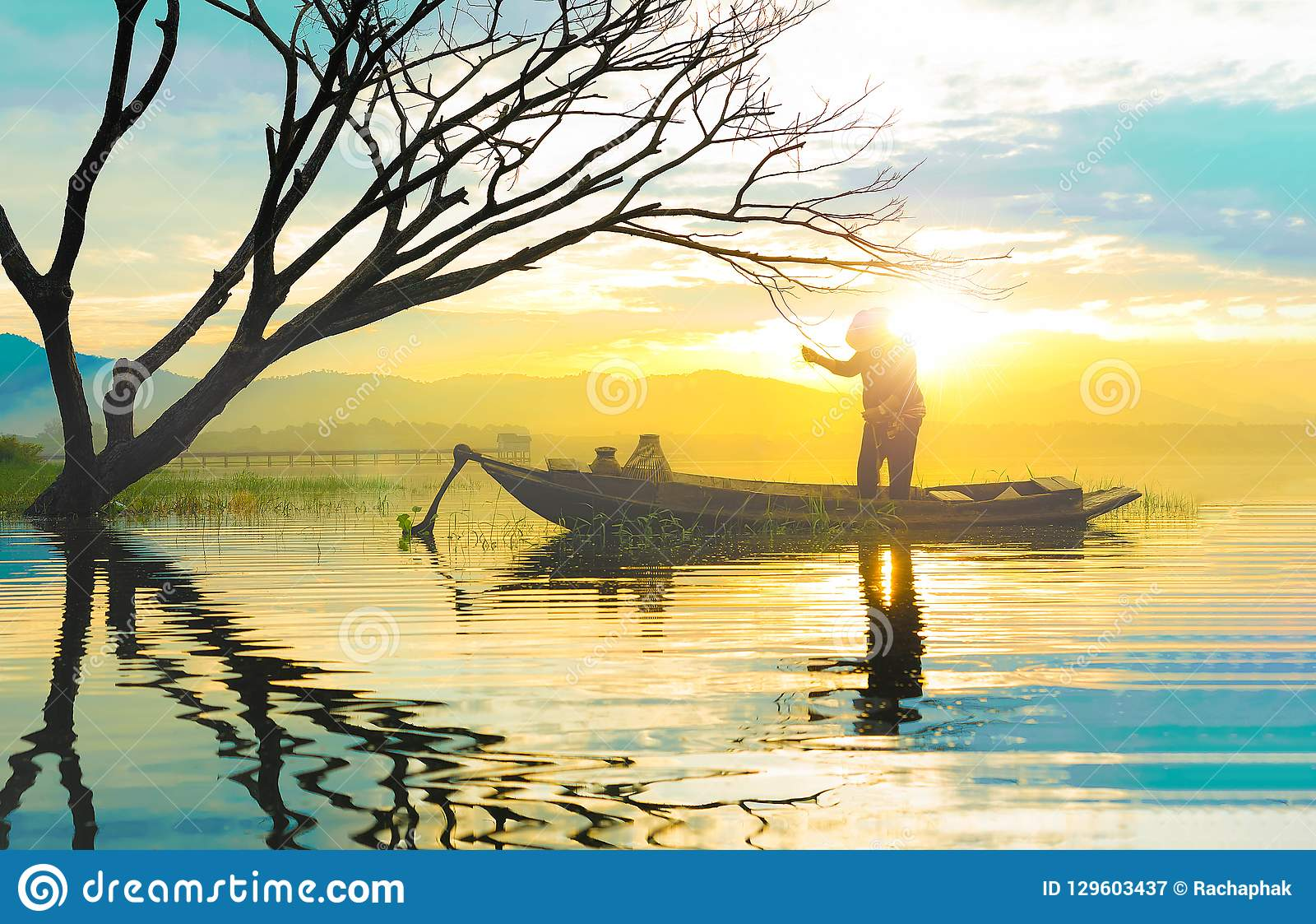 Silhouette of fisherman using fishnet standing in small boat ear