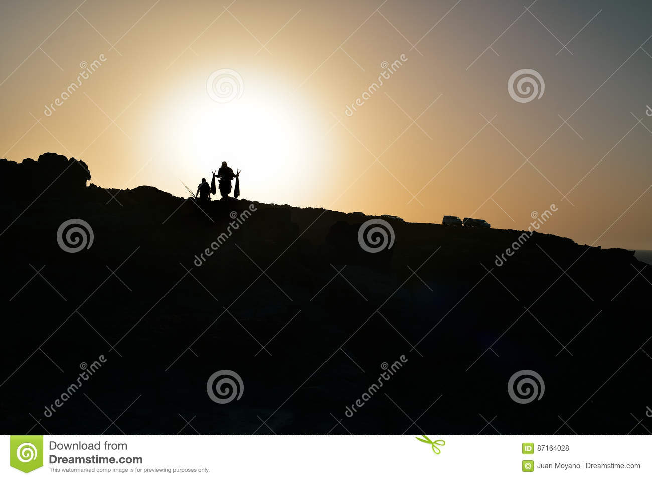 Silhouette of fishermen on a cliff at dusk