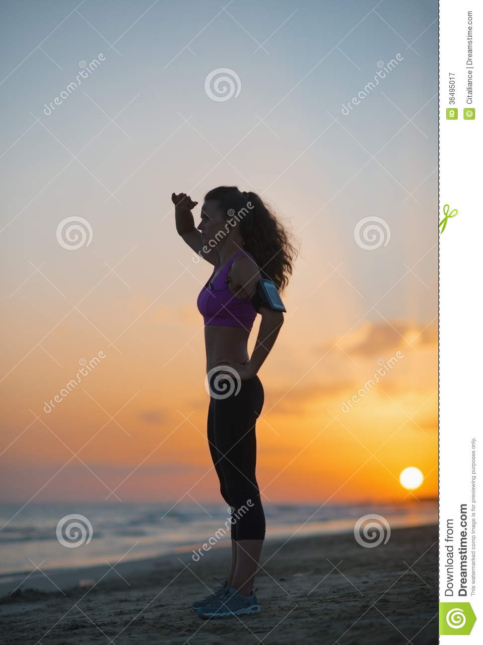 Silhouette Of Fitness Woman Looking Into Distance On Beach