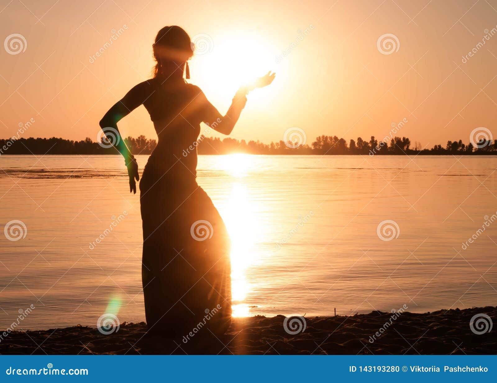 Silhouette foncée de la danse de femme trible près de la côte de rivière