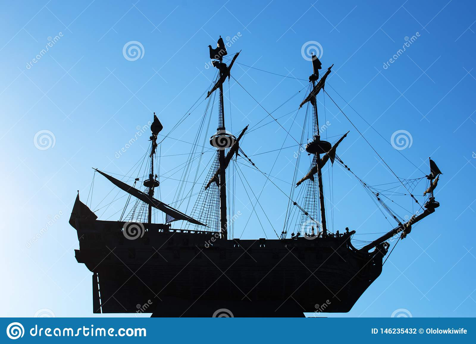 Silhouette of a frigate on a blue clear sky. Three-masted sailing ship soaring in the air