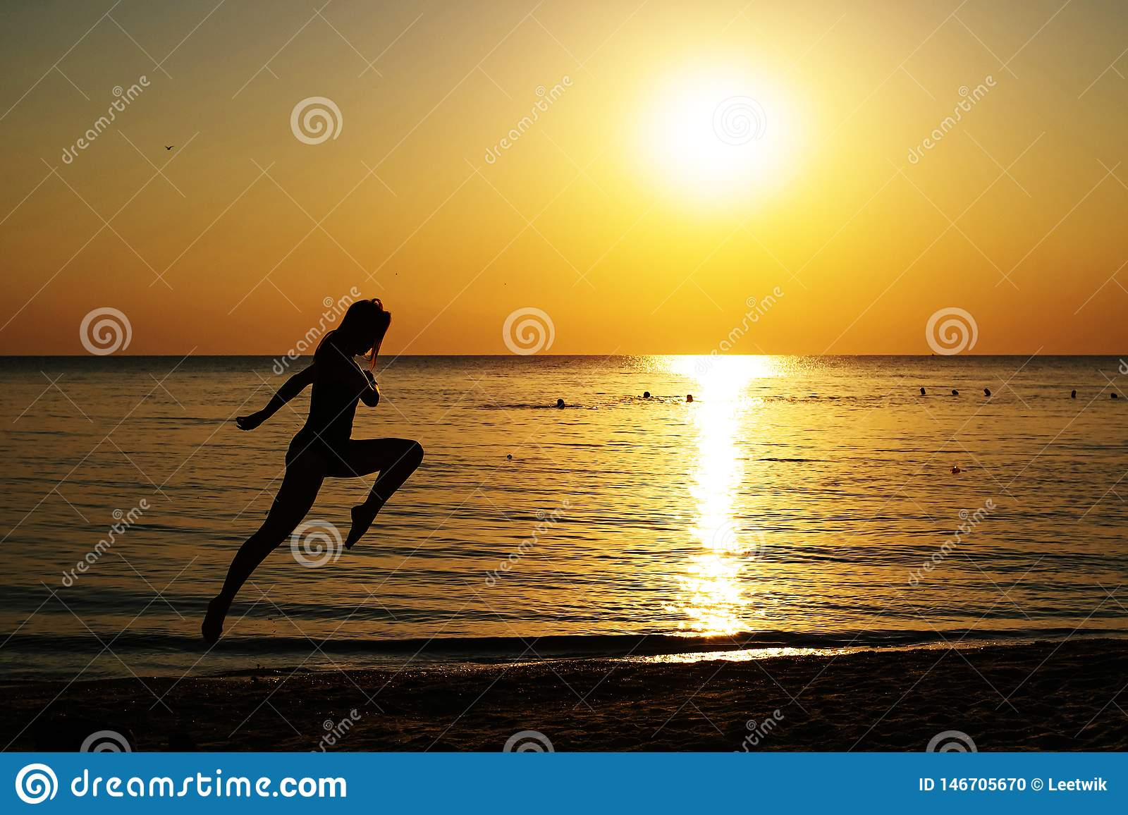 Silhouette of a girl in a bathing suit running along the beach on the background of the dawn