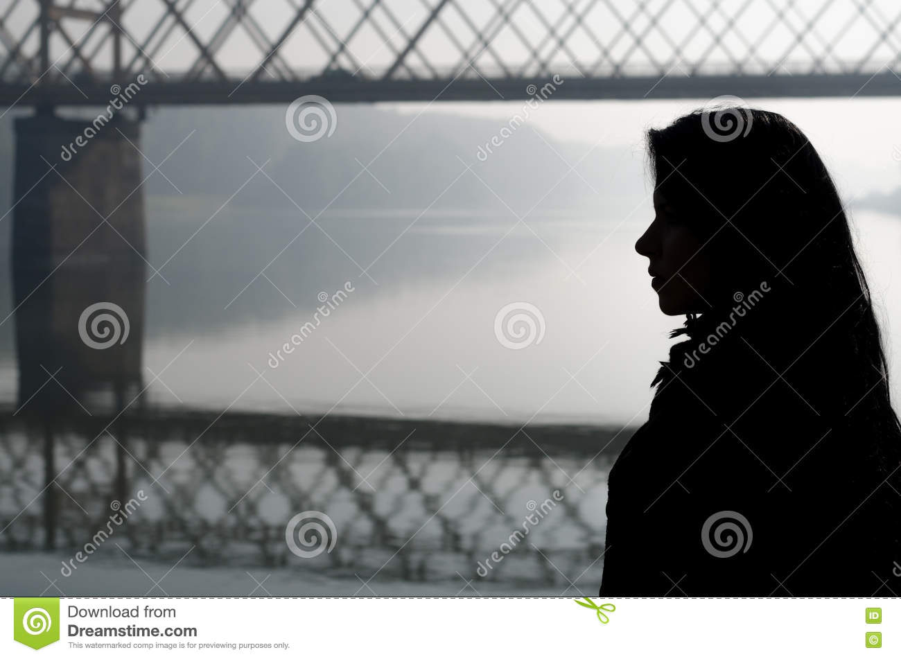 Silhouette of girl and bridge over river on beautiful autumn day