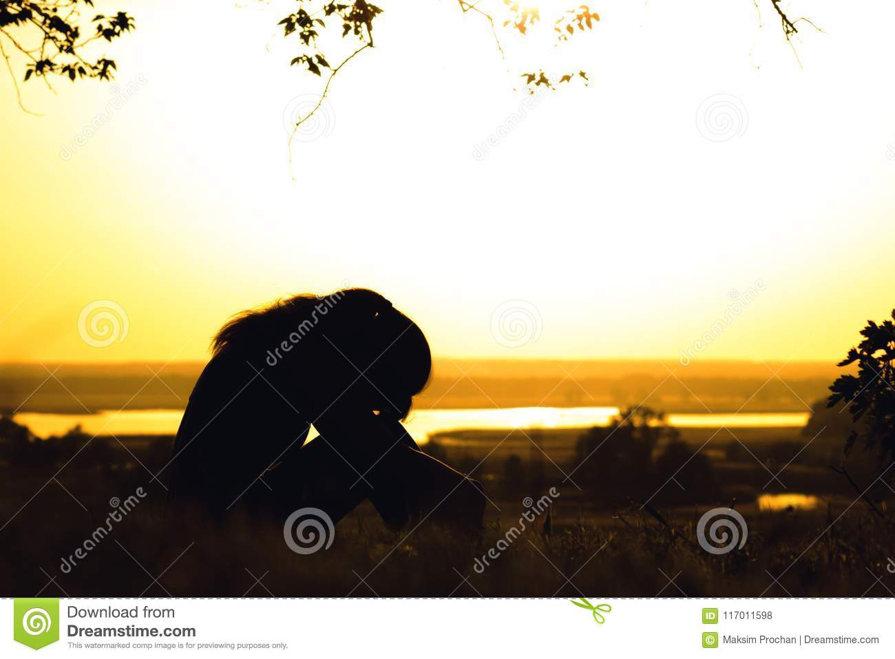 Silhouette of a girl exhausted after physical training, a woman tilted head to knees at sunset