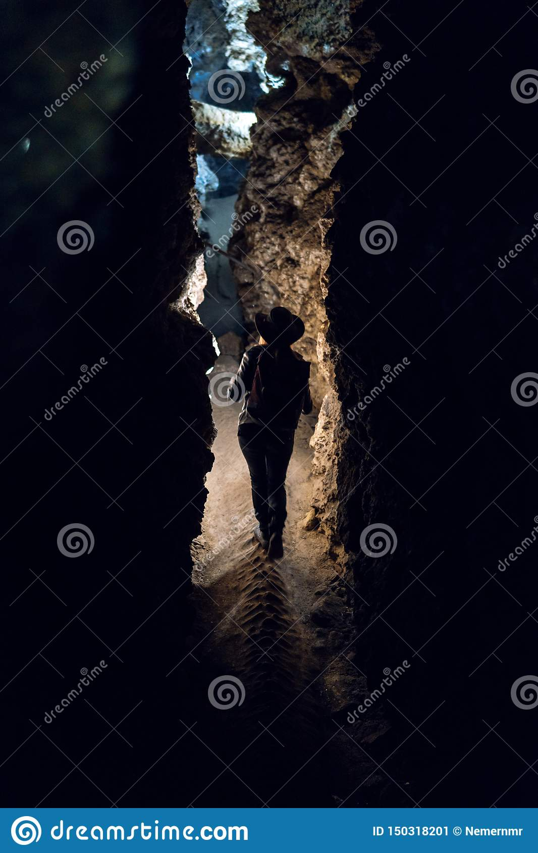 Silhouette Girl exploring huge cave. Adventure traveller dressed cowboy hat and backpack, leather jacket. vertical photo, tourist