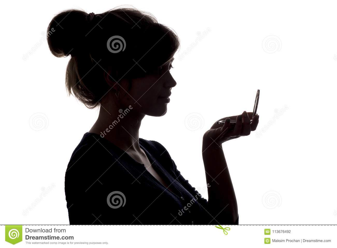 Silhouette of a girl with handpicked hair, profile of a woman face looking in a pocket mirror, the concept of the beauty and fashi