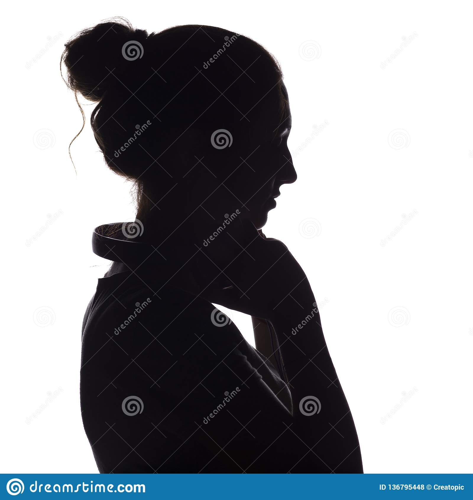 Silhouette of a girl with with headphones around neck, a young woman listening to music on a white isolated background, concept of