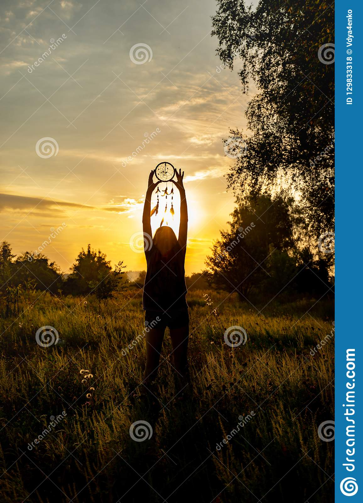 Silhouette of a girl holding an amulet high above her head. The keeper of wishes and dreams.
