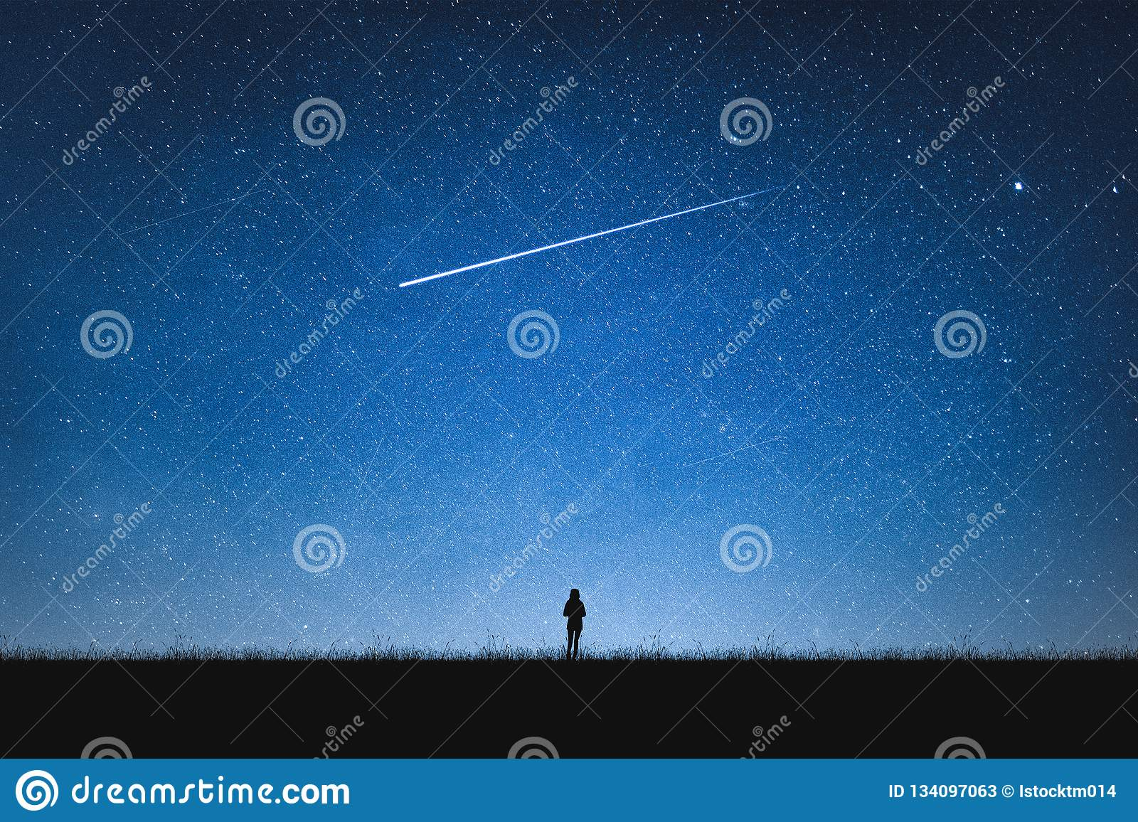 Silhouette of girl standing on mountain and night sky with shooting star. Alone concept
