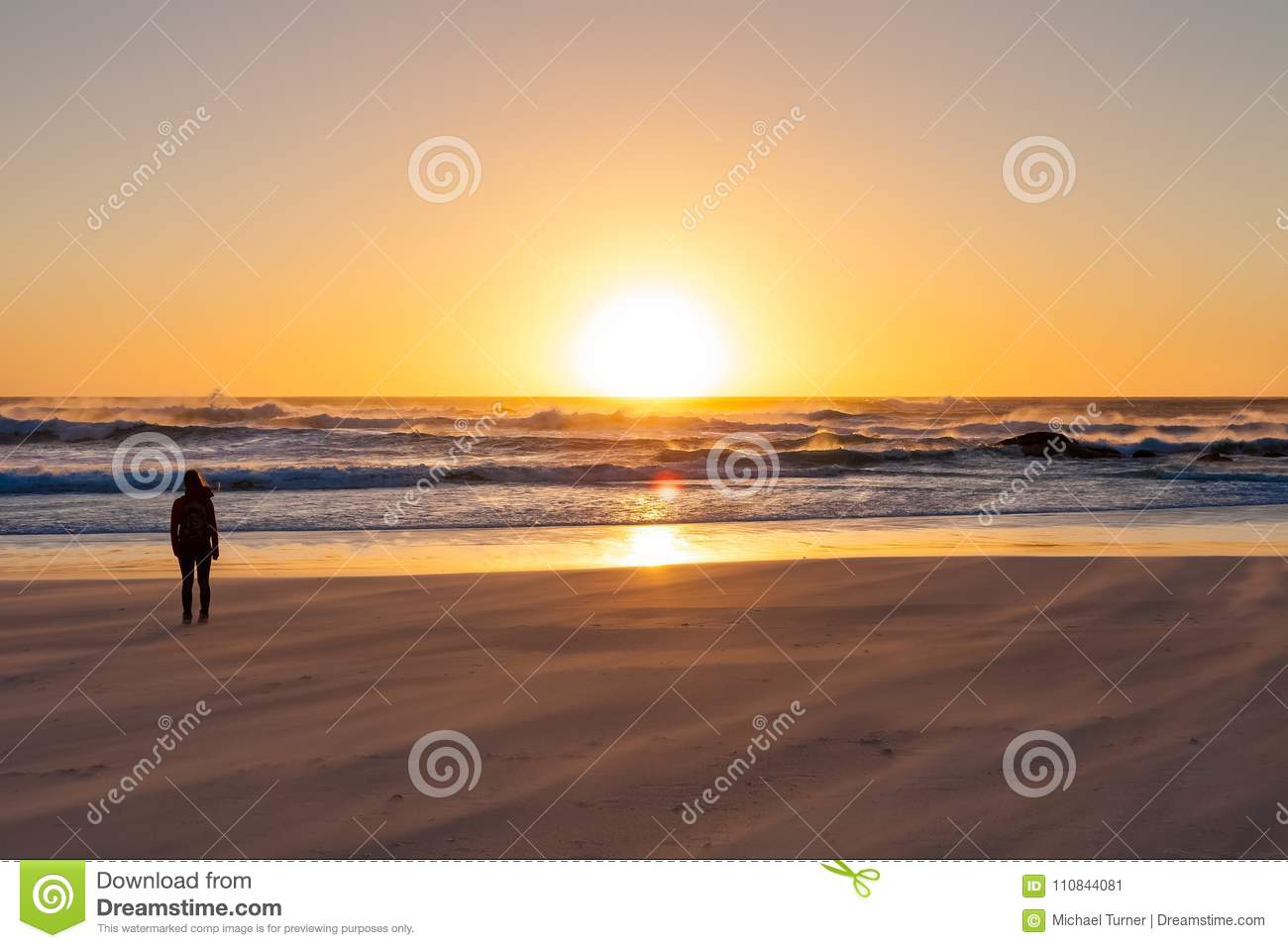 Silhouette girl watching a sunset on a sandy beach with rough ocean wind.
