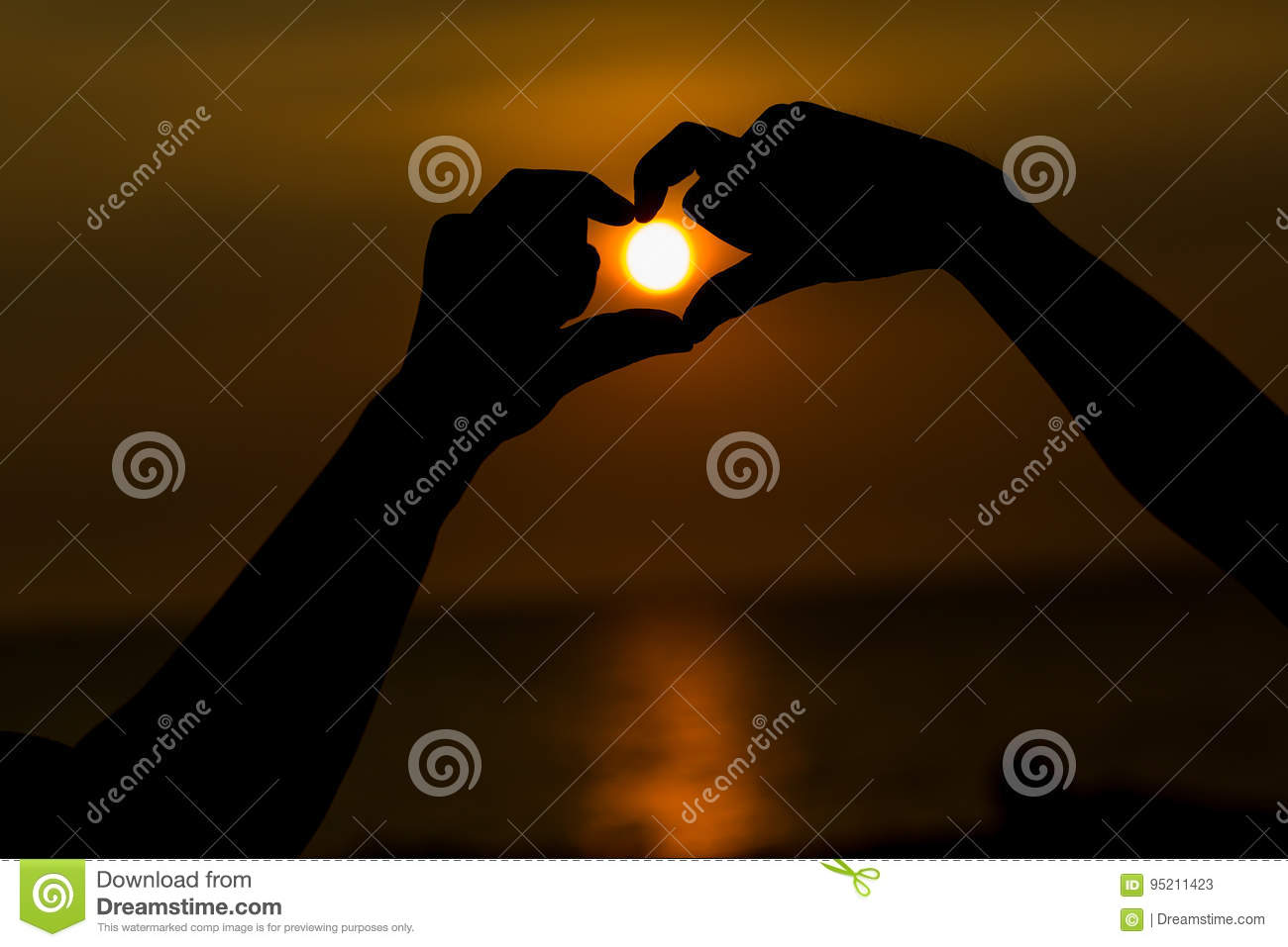 Silhouette of hands making a heart shaped symbol with beautiful sunset background.