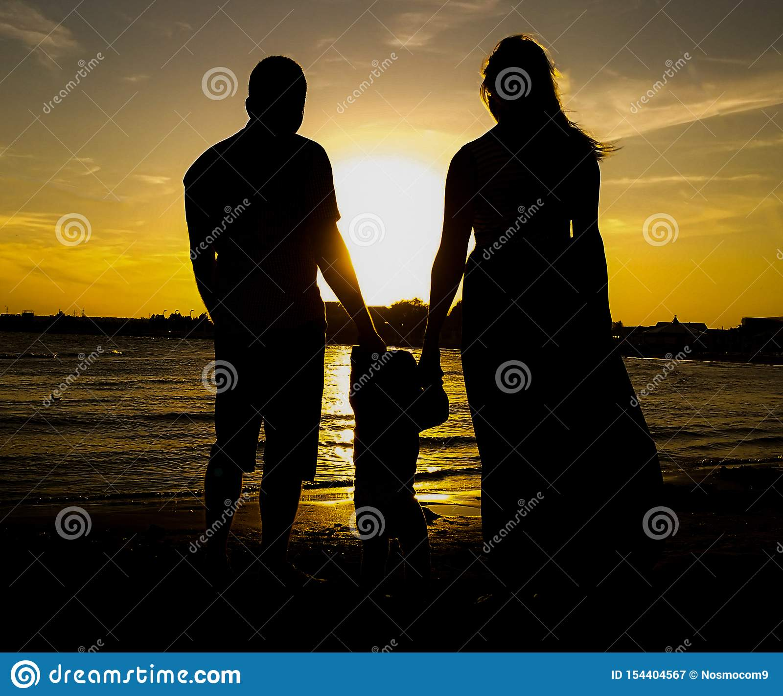 Happy family standing on beach against sky during sunset. Father, mother and daughter who are holding their hands