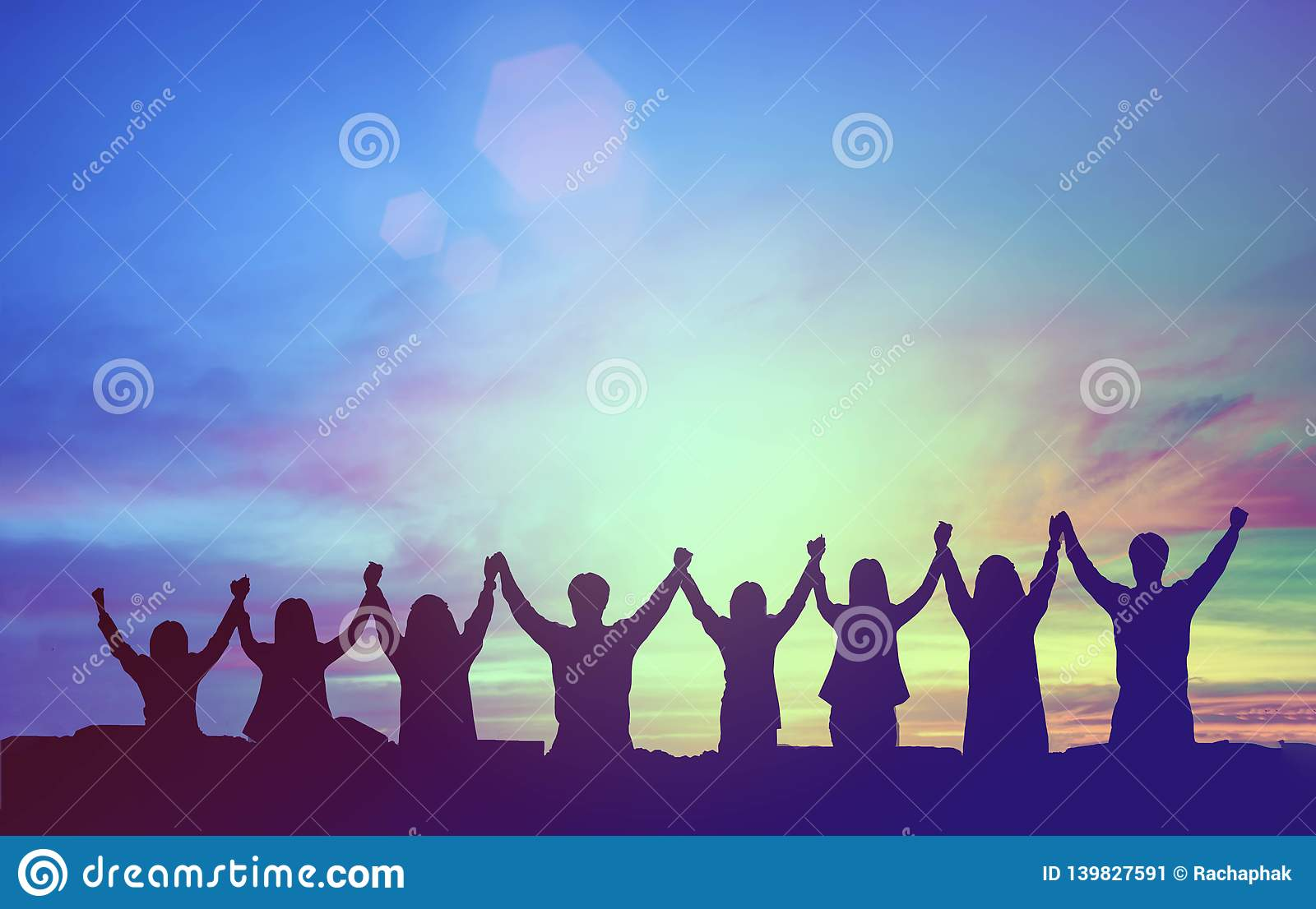 Silhouette of happy teamwork hold hands up as a business successful, victory. Business goal achievement, hit company target.