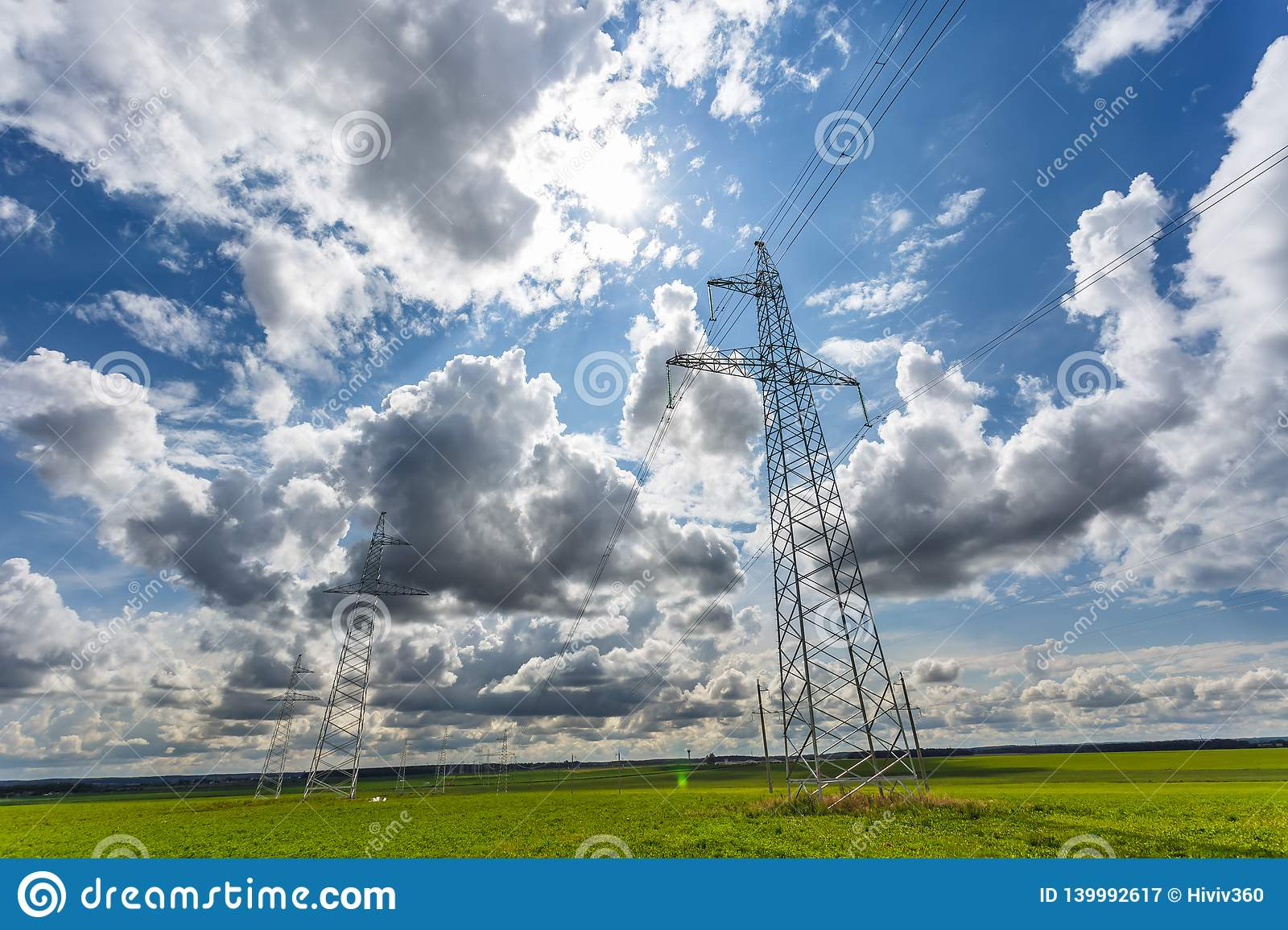 Silhouette of the high voltage electric pylon towers on the background of beautiful clouds