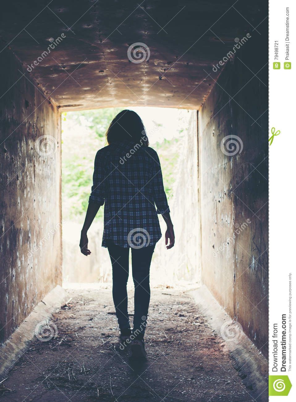Silhouette of hipster woman walk in tunnel. Light at End of Tun