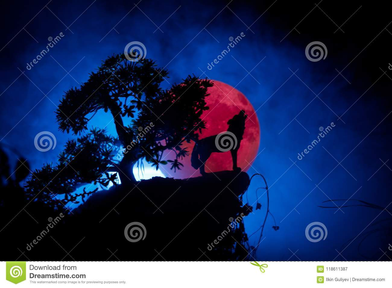 Silhouette of howling wolf against dark toned foggy background and full moon or Wolf in silhouette howling to the full moon. Hallo