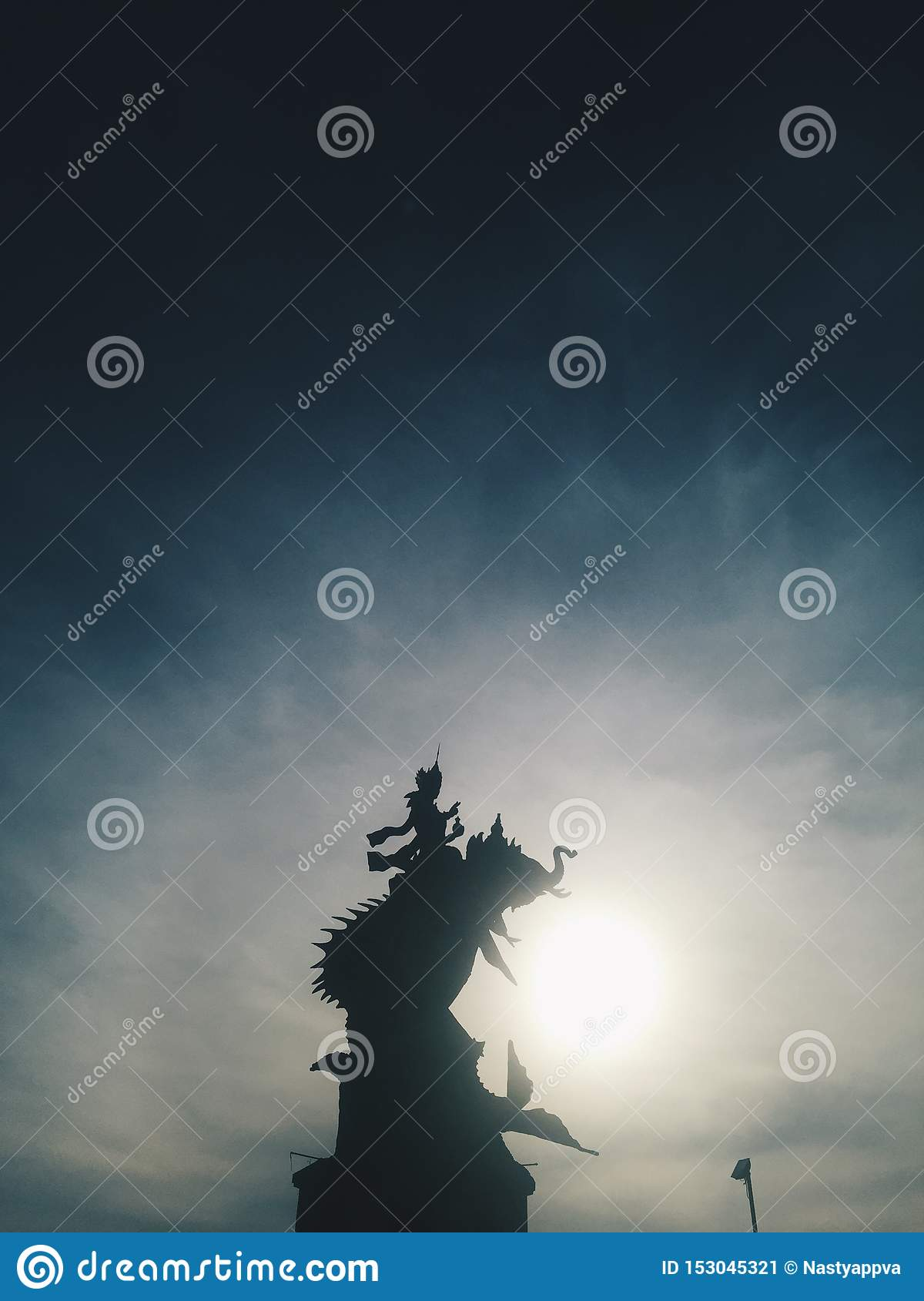 Silhouette of Indonesian statue at blue sky at background at sunset