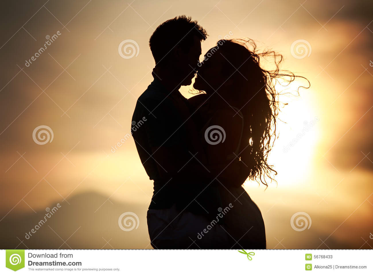 silhouette of kissing guy and girl at dawn