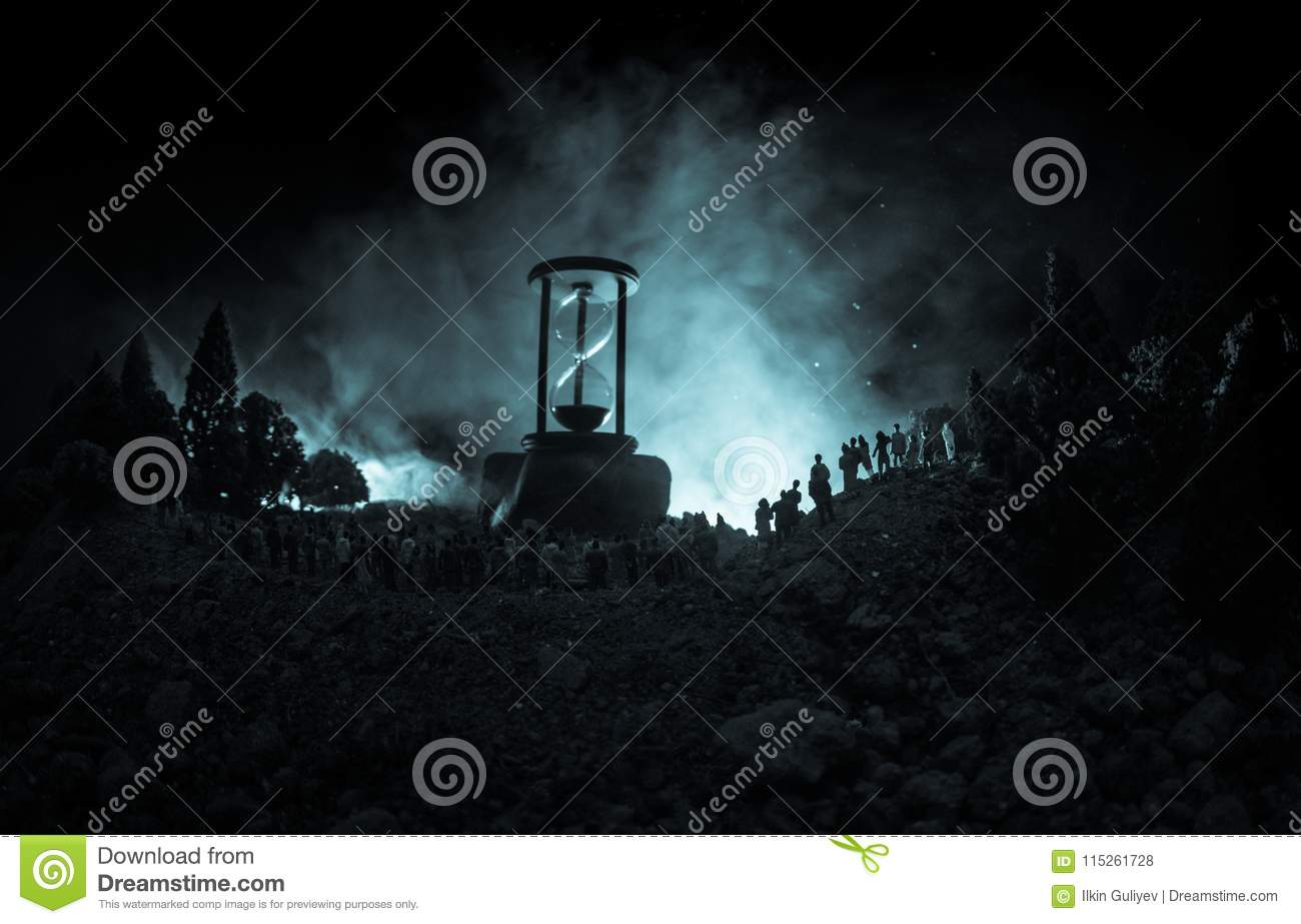 Silhouette of a large crowd of people in forest at night standing against a big hourglass with toned light beams on foggy backgrou