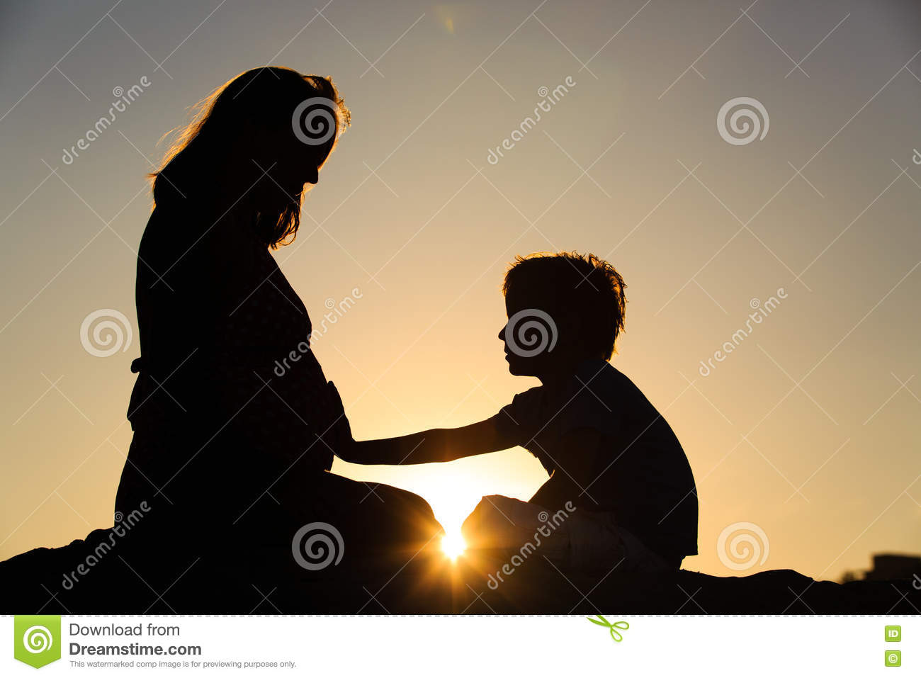 Silhouette of little boy touching pregnant mother tummy