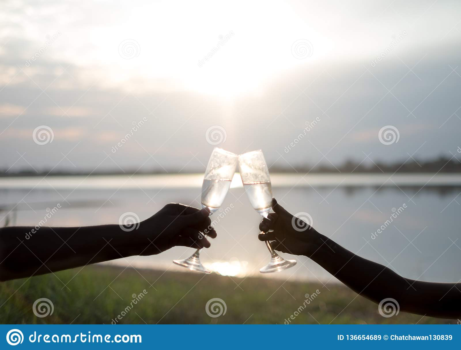 Silhouette. Lovers hand with glasses of champagne against the sunset and sky background