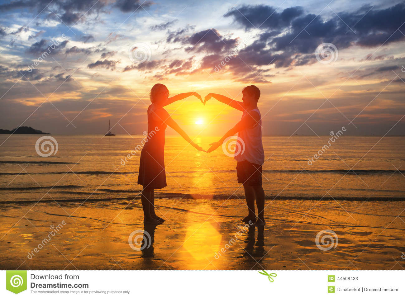 Silhouette of loving couple during an amazing sunset, holding hands in heart shape. Love.