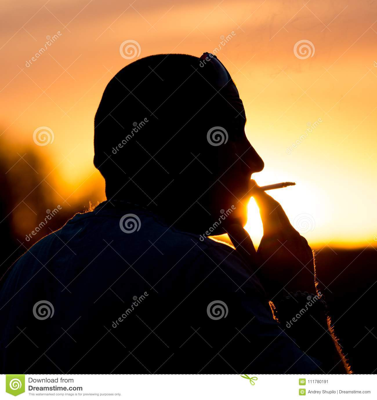 Silhouette of male smokers in the sunset