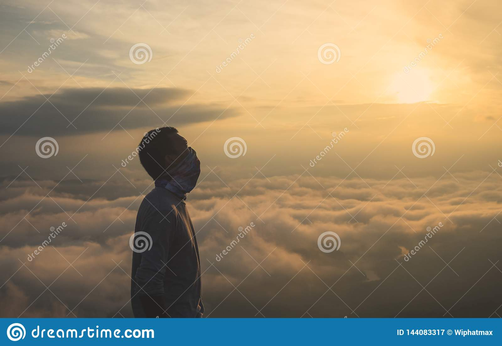 Silhouette of male in sunrise background.