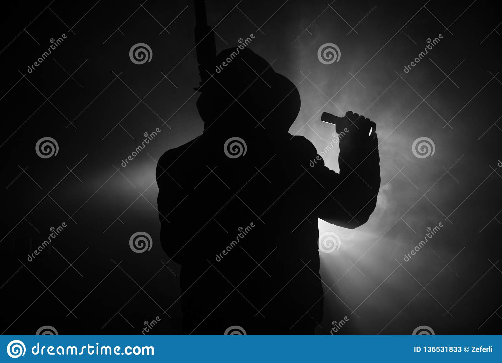 Silhouette of man with assault rifle ready to attack on dark toned foggy background or dangerous bandit in black wearing balaclava