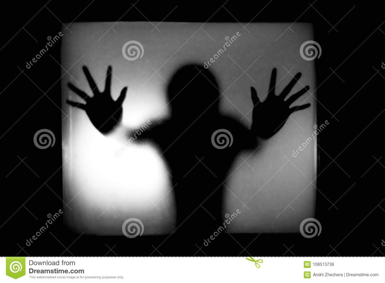Silhouette of a man behind glass trying to escape in horror