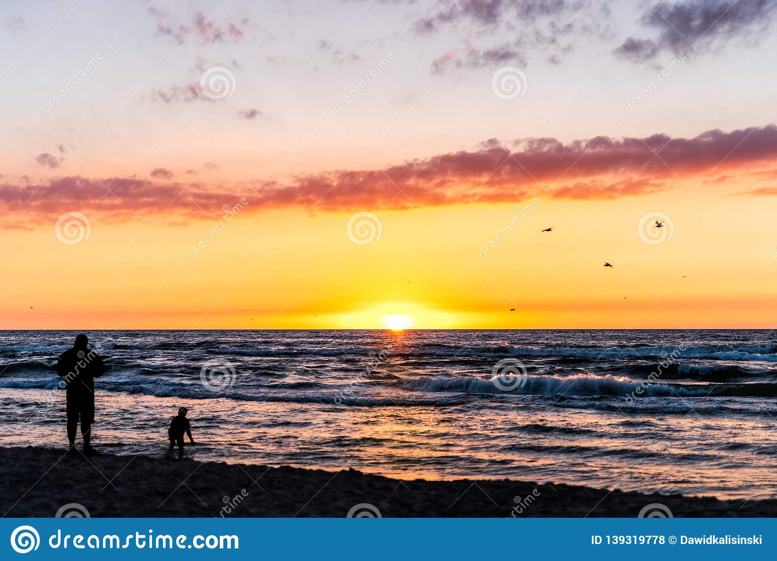 Silhouette of a man and child playing at the beach with beautiful sunset over sea