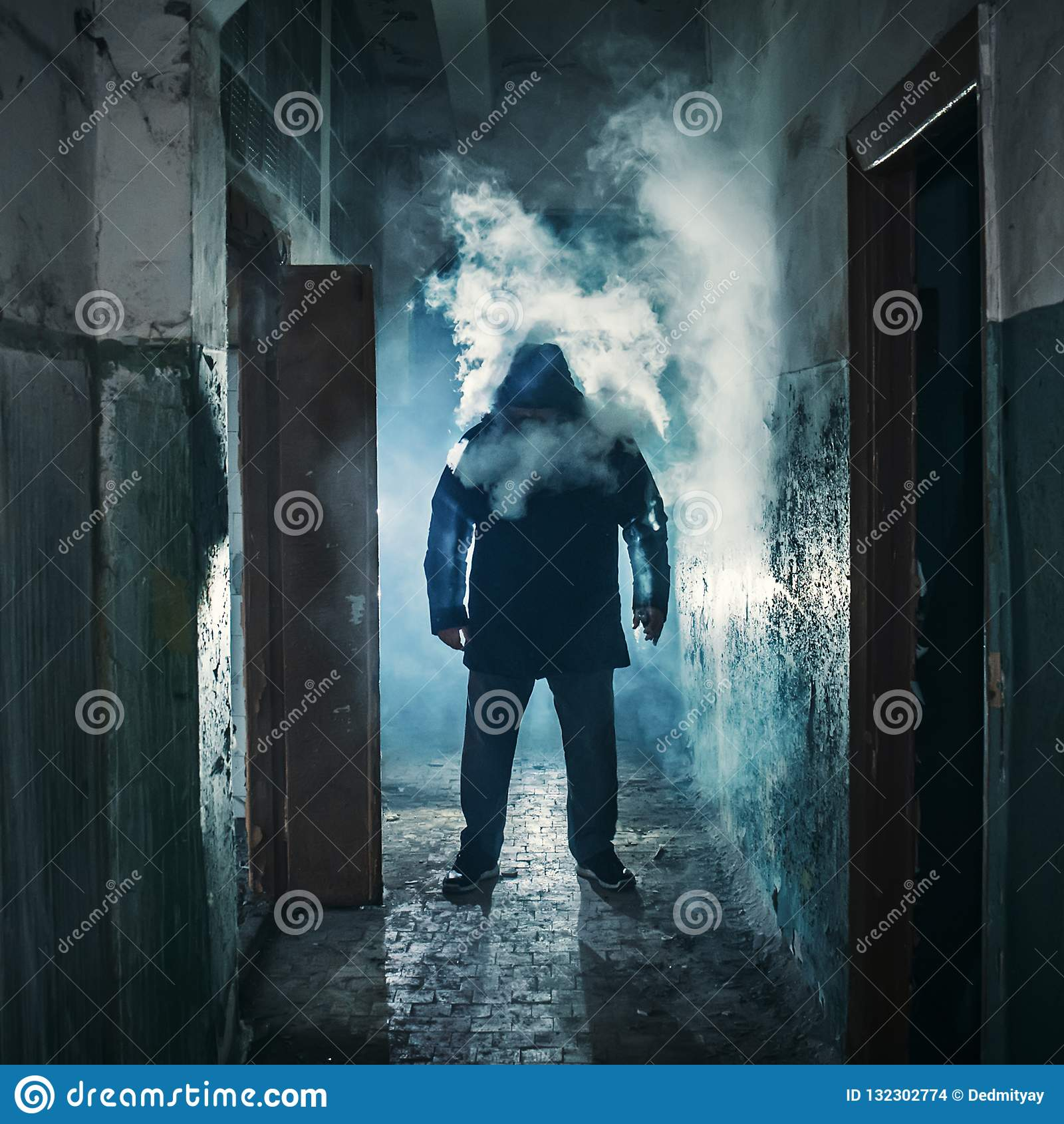 Silhouette of man in dark creepy corridor in clouds of vape steam or vapor smoke, mystery horror atmosphere