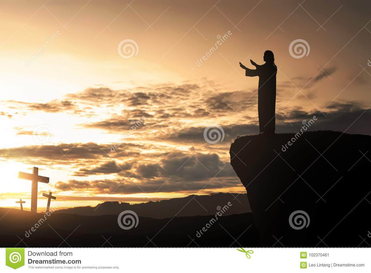 Silhouette of man facing the cross and praying