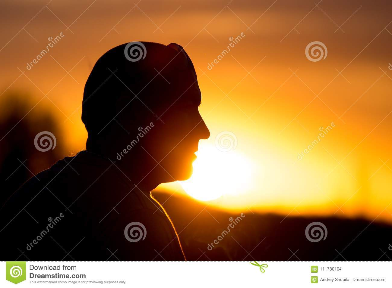 Silhouette of a man with glasses on sunset