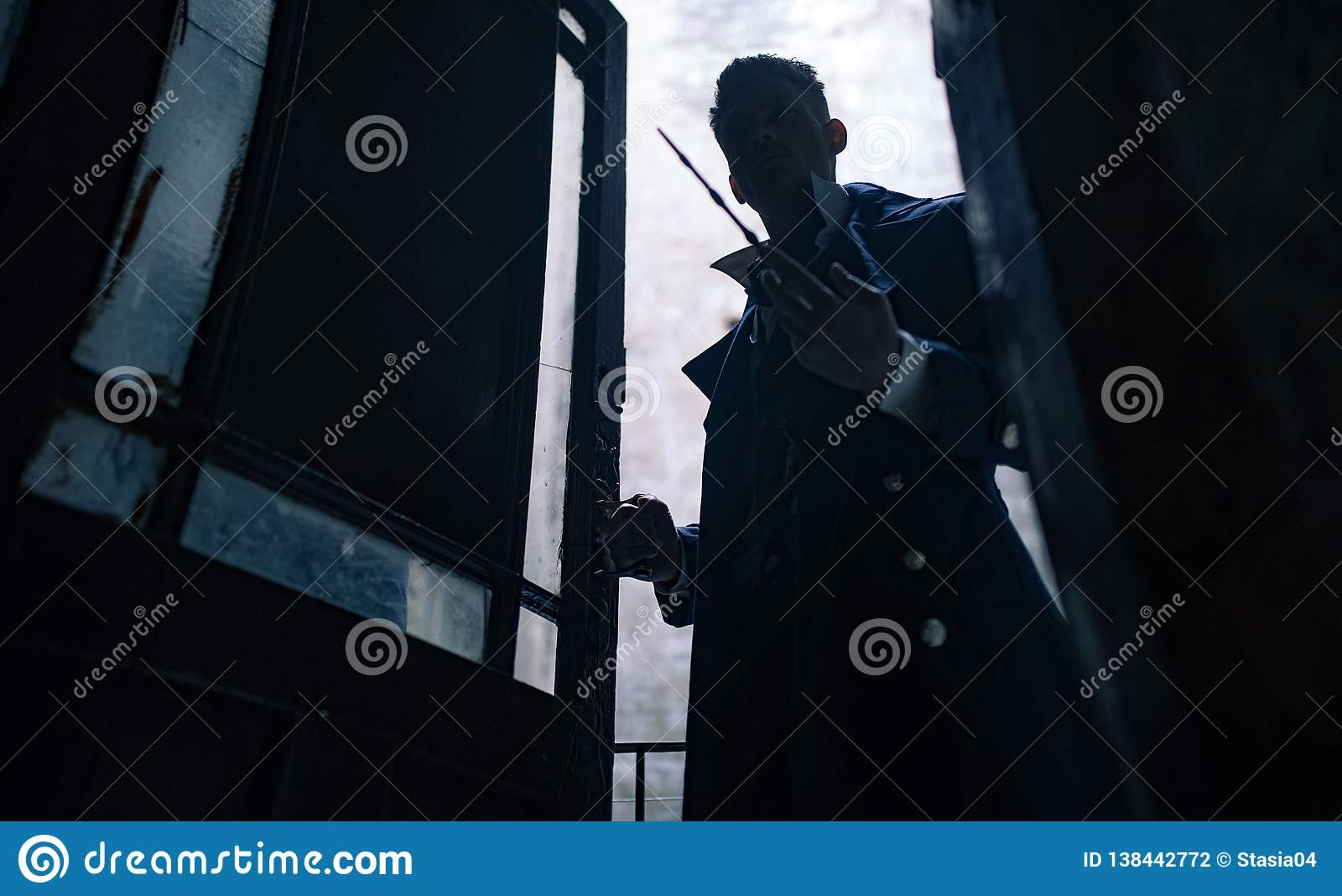 Silhouette of man in image of black magician with magic wand in his hand