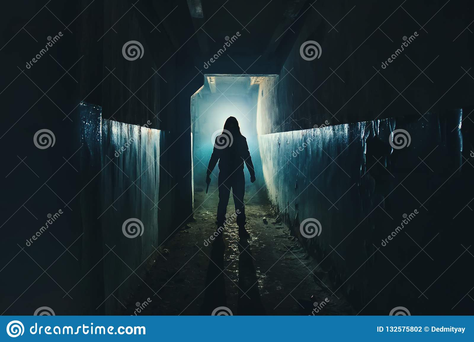 Silhouette of man maniac or killer or horror murderer with knife in hand in dark creepy and spooky corridor. Criminal robber
