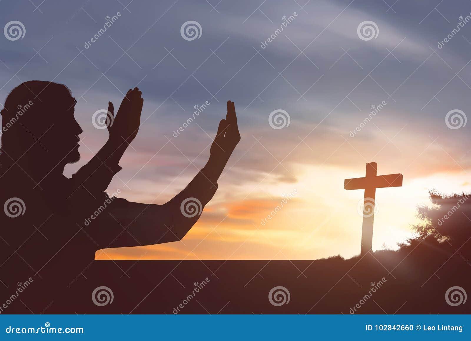 Silhouette man raising hand while praying to jesus