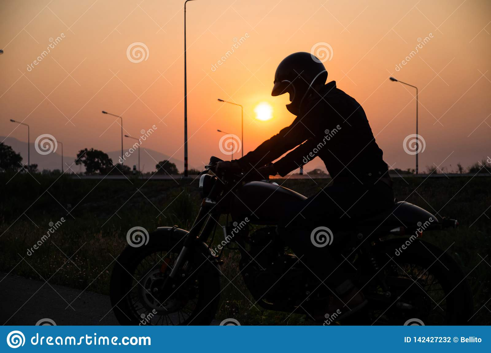 Silhouette of man riding vintage motorcycle cafe racer style with helmet