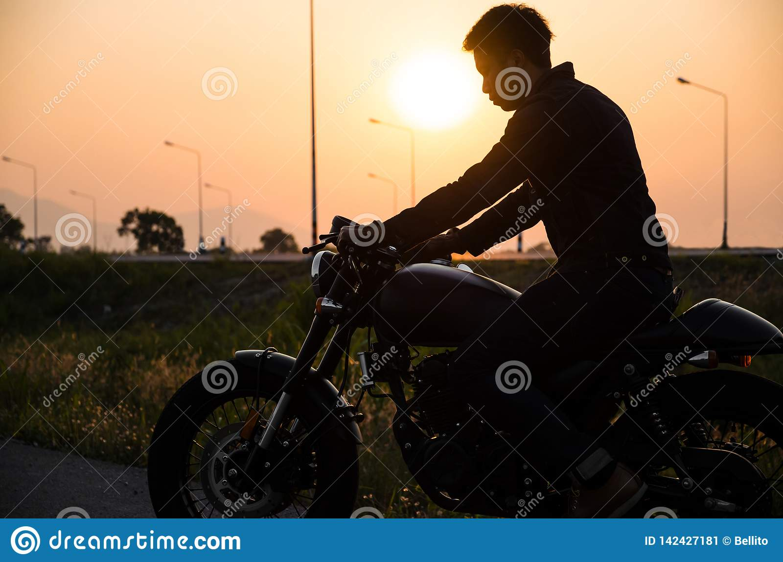 Silhouette of man riding vintage motorcycle cafe racer style