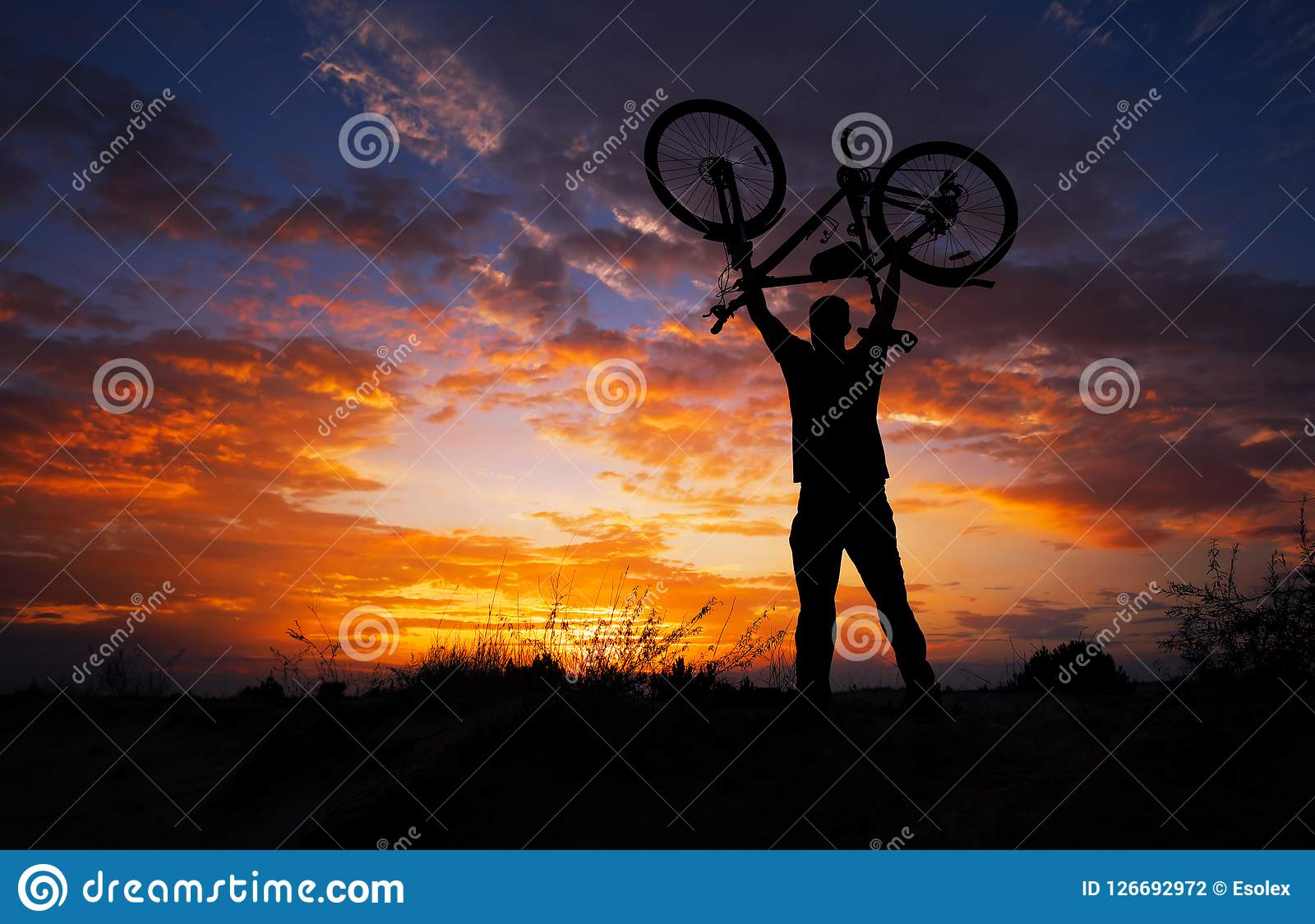 Silhouette the man stand in action lifting bicycle