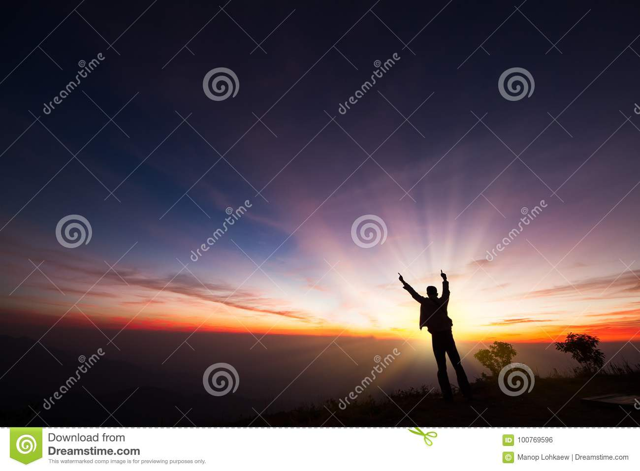 Silhouette of a man standing on the cliff looking at sunrise background, hope and following a dream concept