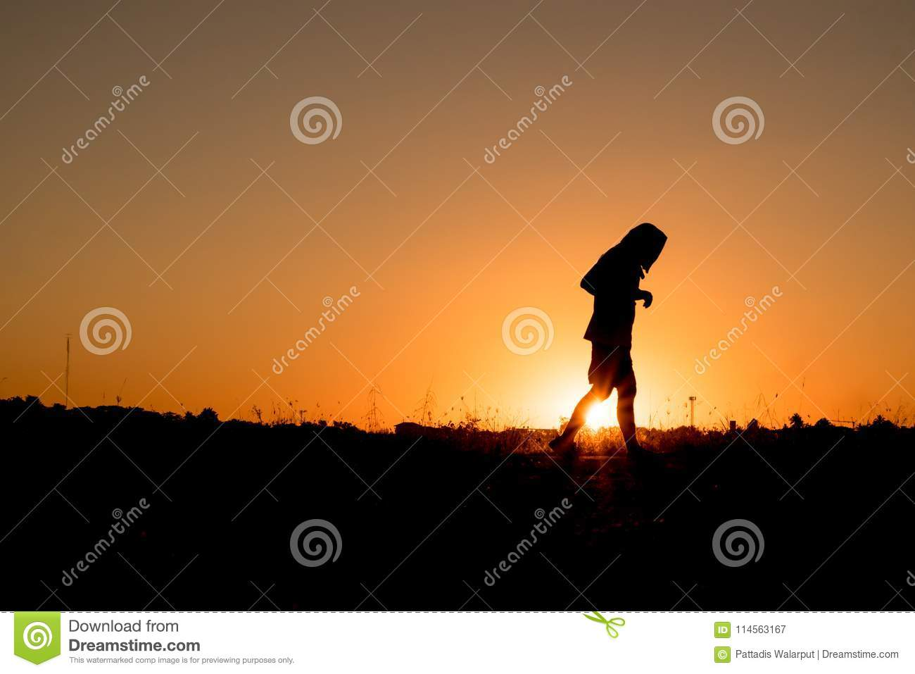 Silhouette of a man walking or jogging for exercise in the park at sunset.