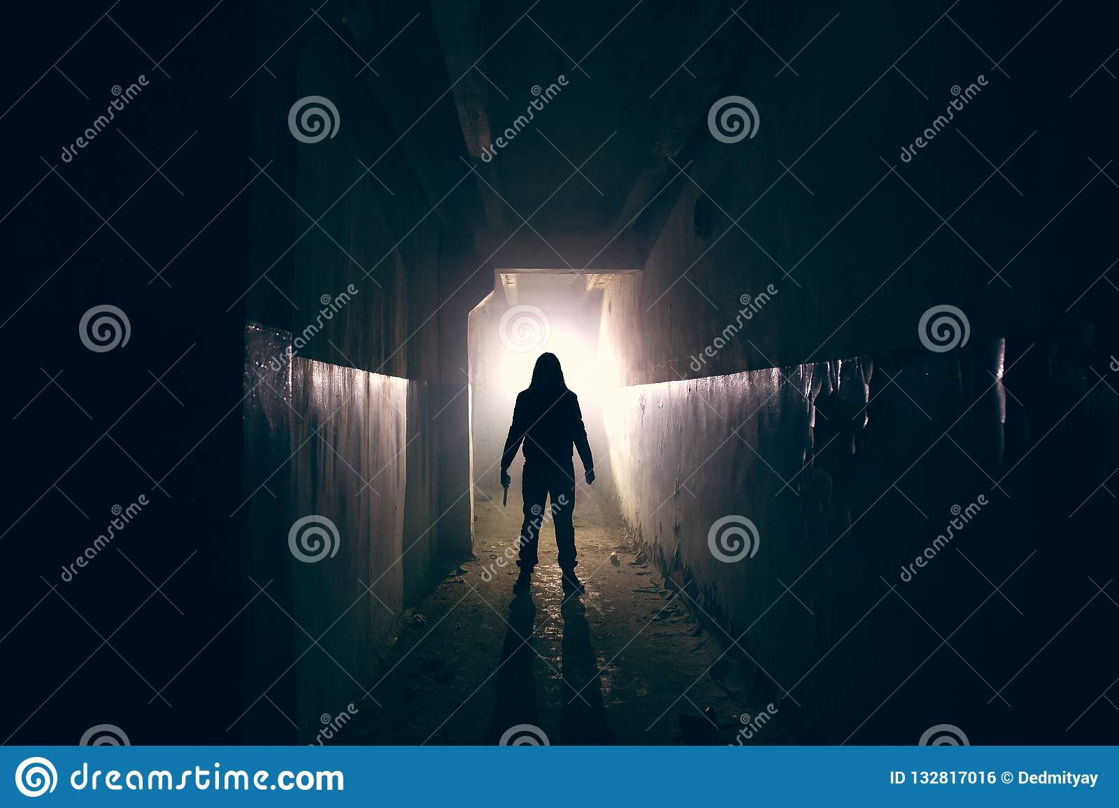 Silhouette of maniac with knife in hand in long dark creepy corridor, horror psycho maniac or serial killer concept
