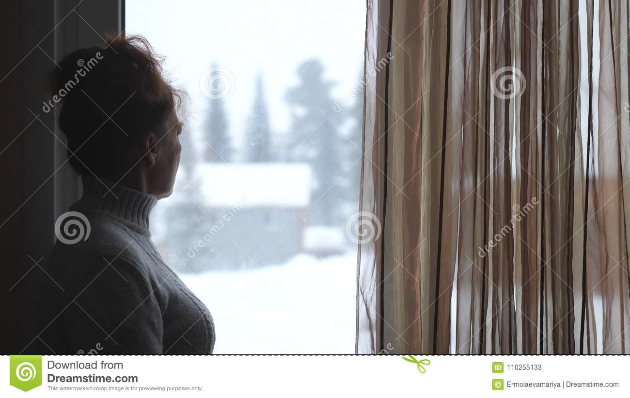 Silhouette of mature woman in aged watching in window on snowy mountains