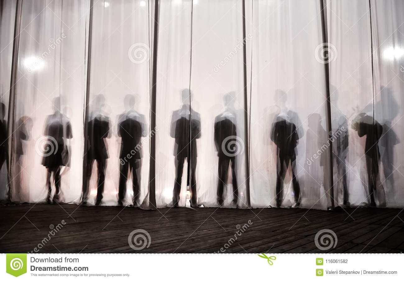 The silhouette of the men behind the curtain in the theater on stage, the shadow behind the scenes is similar to the white and bla