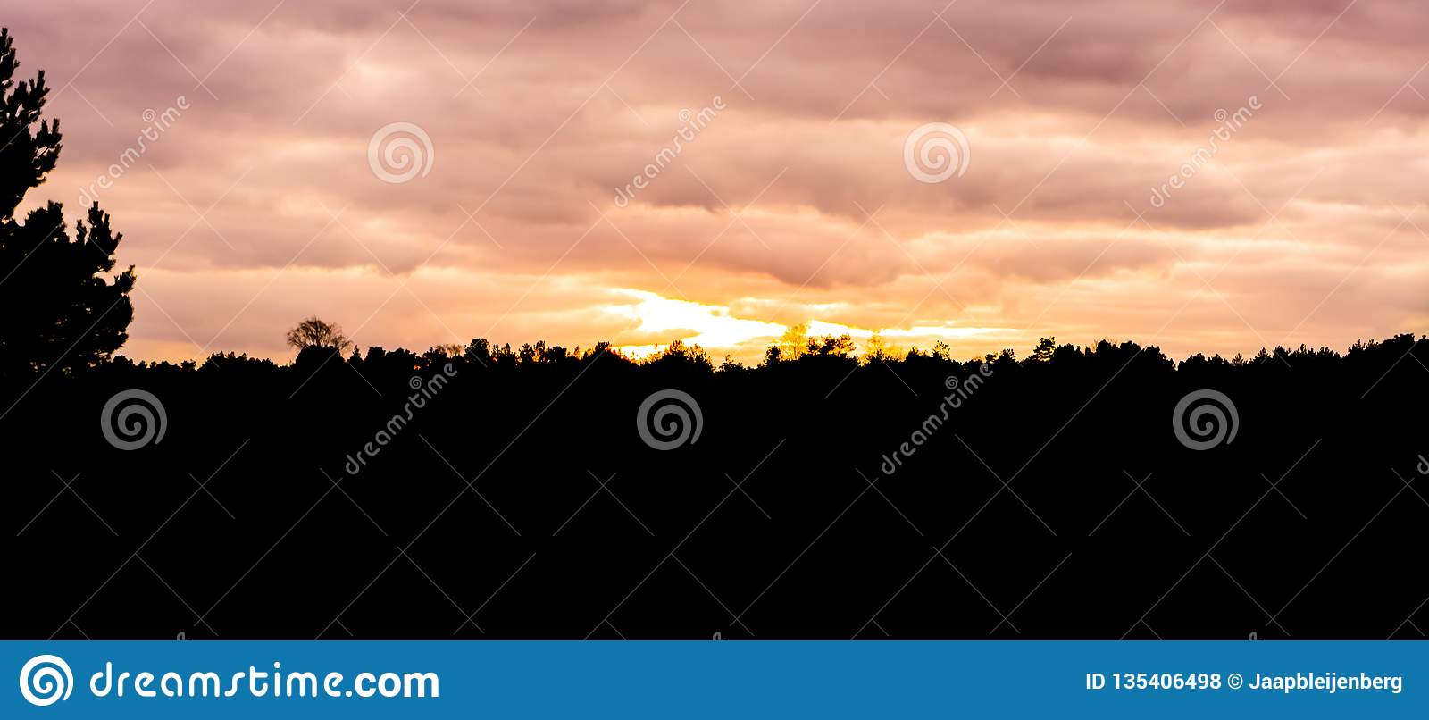 Silhouette of a moorland landscape in the forest at sunset, sundown giving orange and pink colors in the sky and clouds
